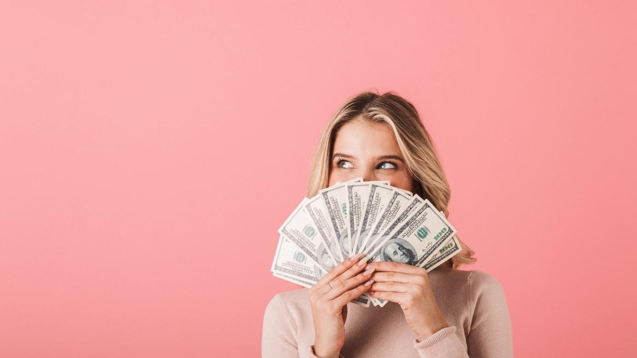 女性がお金を持っている画像
