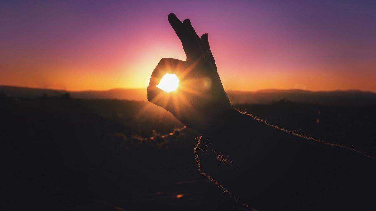 夕日にOKをしている画像